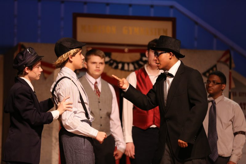 A scene from a school production where young men are having a serious conversation.