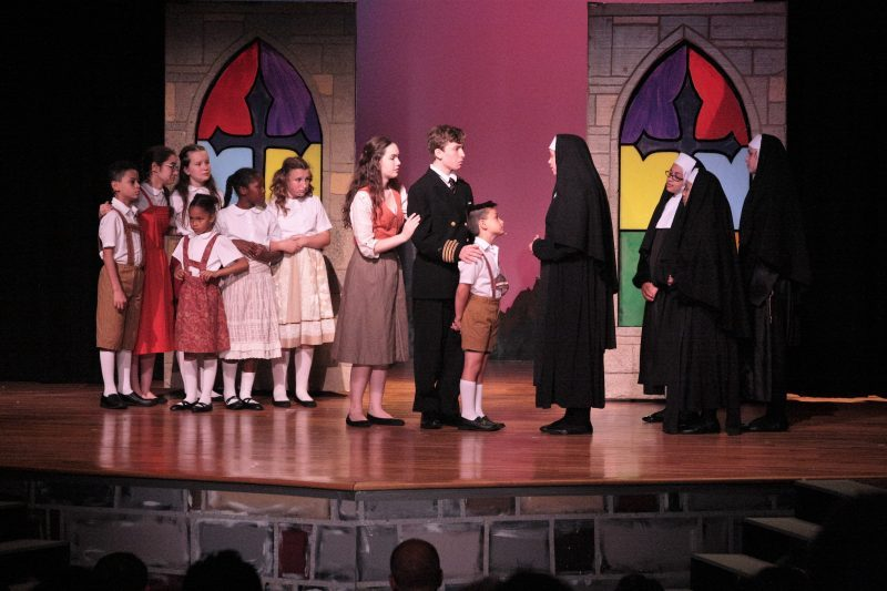 A scene from a production with a nun talking with a young man and woman.