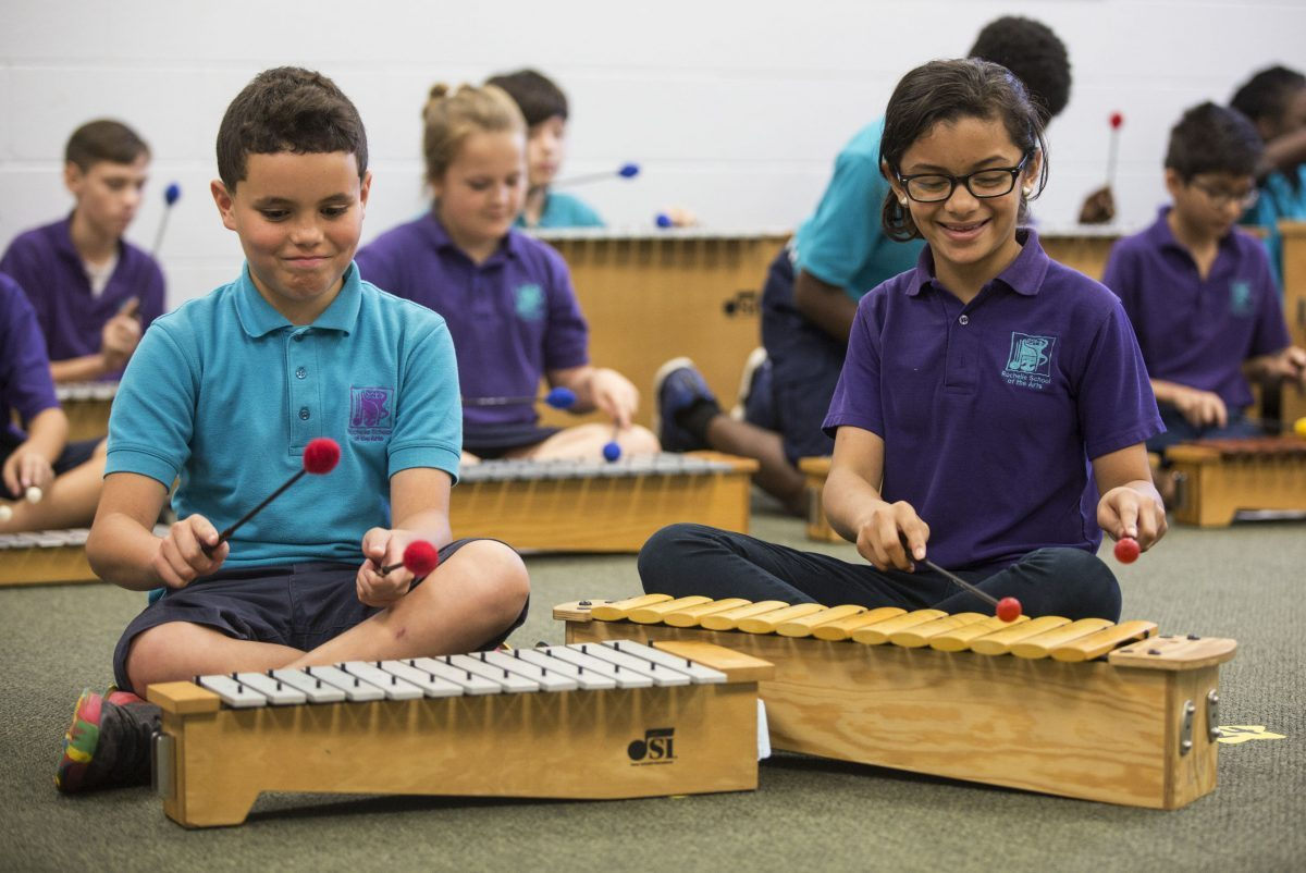 Two young elementary students playing the xylophone in music class.