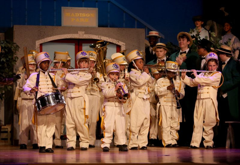 Elementary students acting on stage as a small marching band playing instruments.