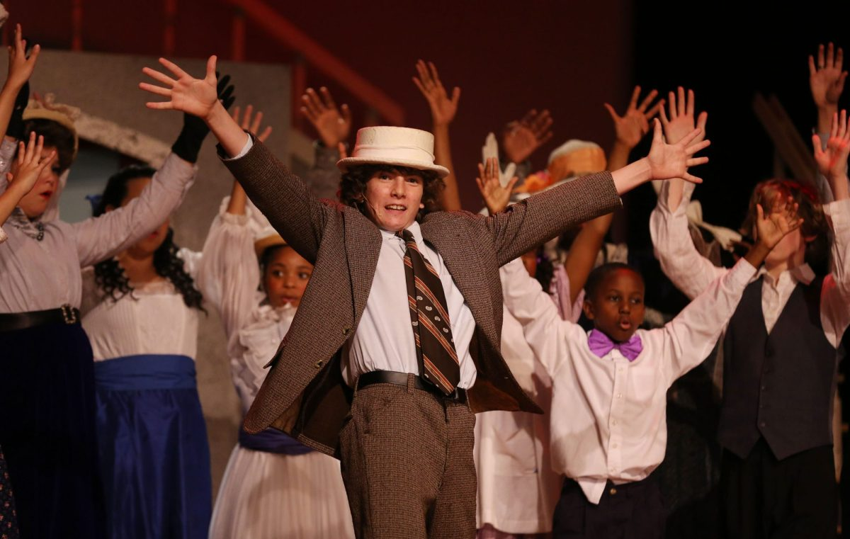 A young boy with his hands open wide as he dances in a school production.