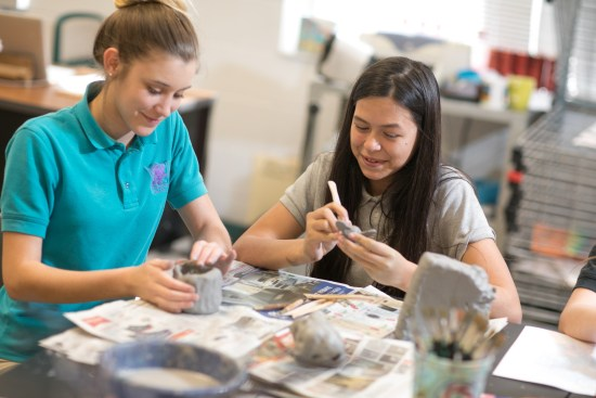 Two middle school girls working together on pottery project.