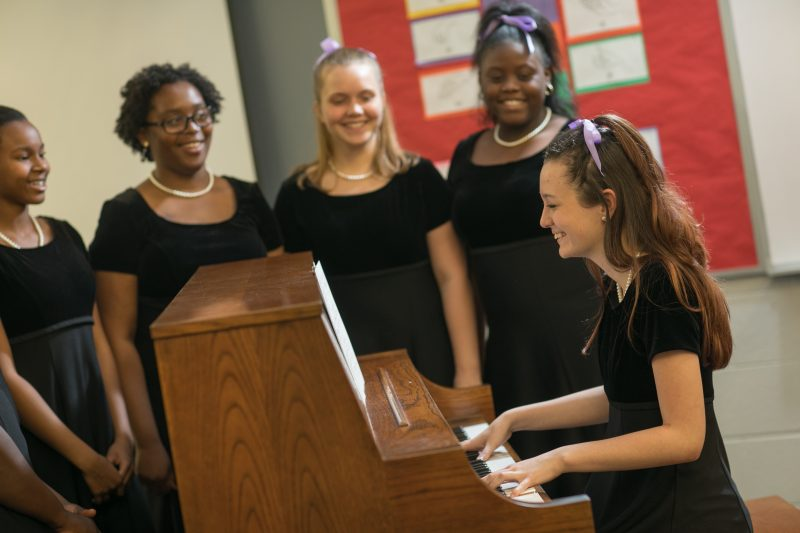 A young girls sits at the piano while four other girls sing.