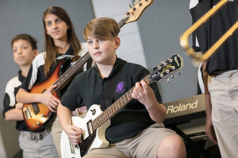 Students playing the bass guitar in music class.