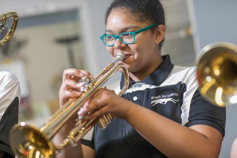 A middle school girl playing the trumpet in music class.